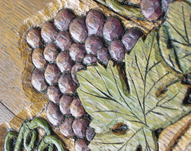 Wine barrel carving - close up of grape wreath clock